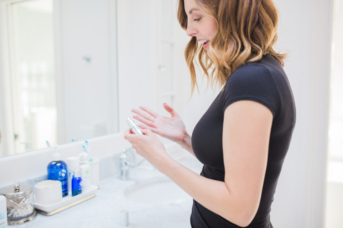 Eva Amurri Martino applying eye cream to her finger in the bright and white bathroom of her connecticut home