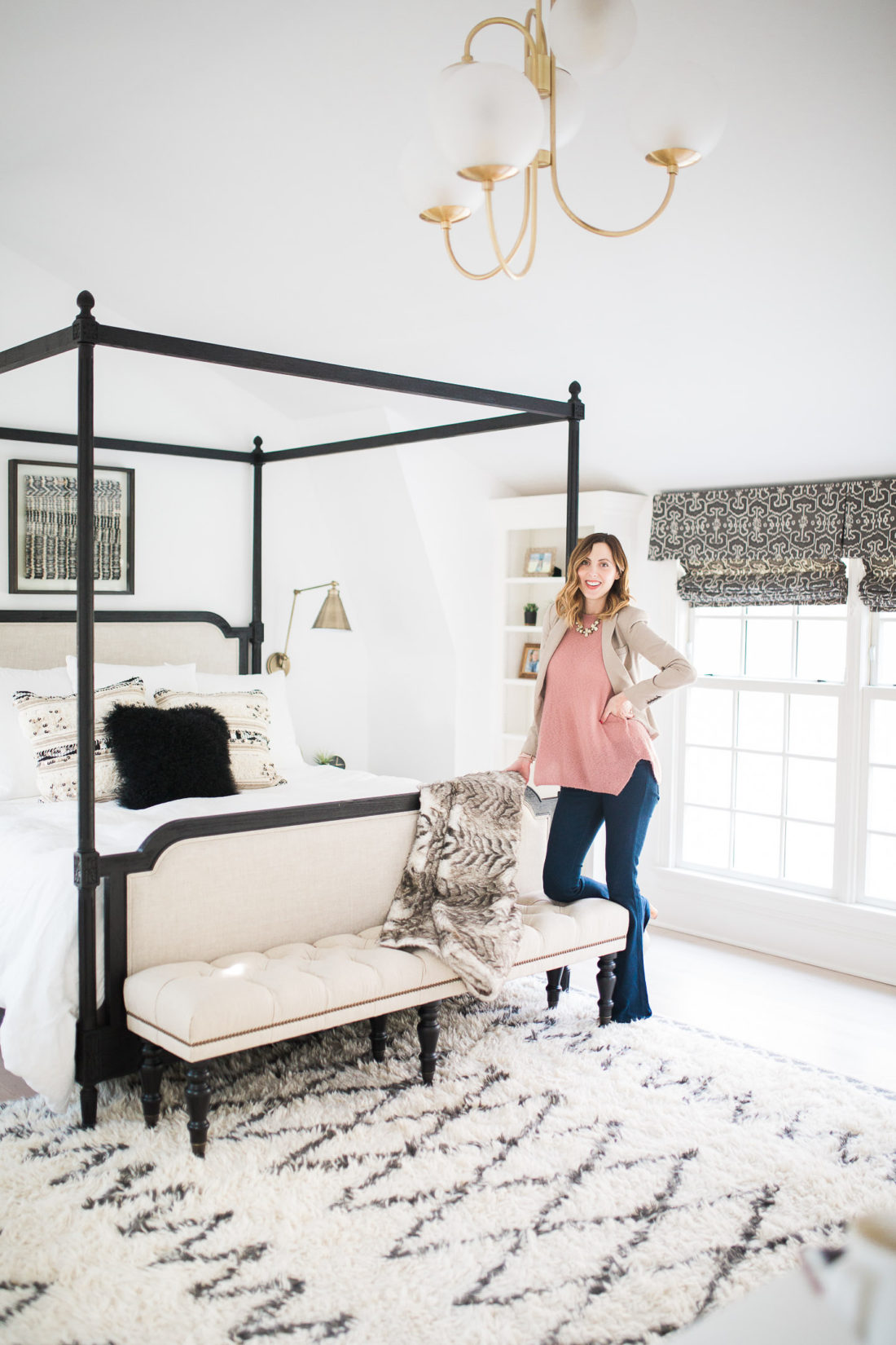 Eva Amurri Martino of lifestyle and motherhood blog Happily Eva After poses in her black, white, and brass master bedroom in Connecticut