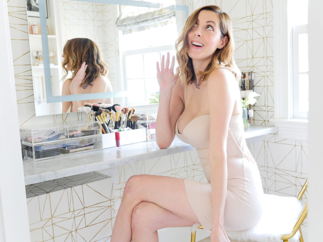 Eva Amurri Martino of lifestyle and motherhood blog Happily Eva After pictured in her glam room wearing a nude Maidenform shapewear slip as she prepares for a holiday party