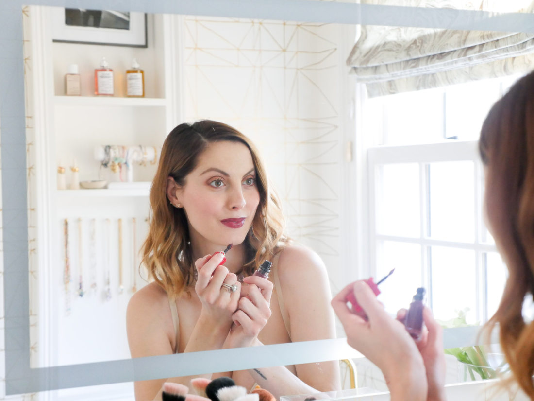 Eva Amurri Martino of lifestlye and motherhood blog Happily Eva After applies lipstick in her maidenform shapewear slip