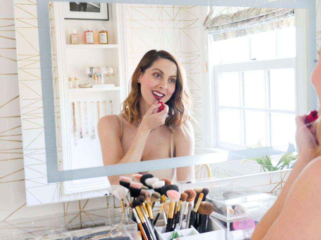 Eva Amurri Martino of lifestlye and motherhood blog Happily Eva After applies lipstick in her maidenform shapewear slip