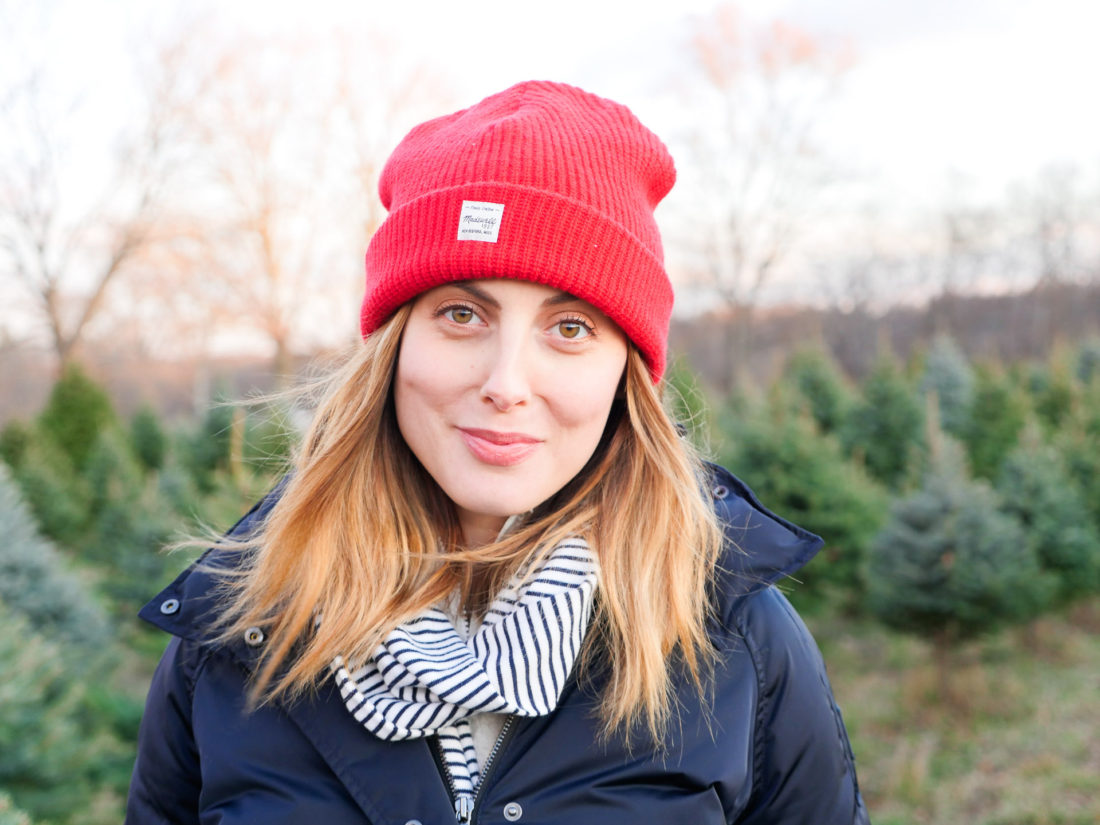Eva Amurri Martino of lifestyle and motherhood blog Happily Eva After wears a navy puffer jacket, blue and white striped scarf and red wool hat at the Christmas tree farm in Connecticut