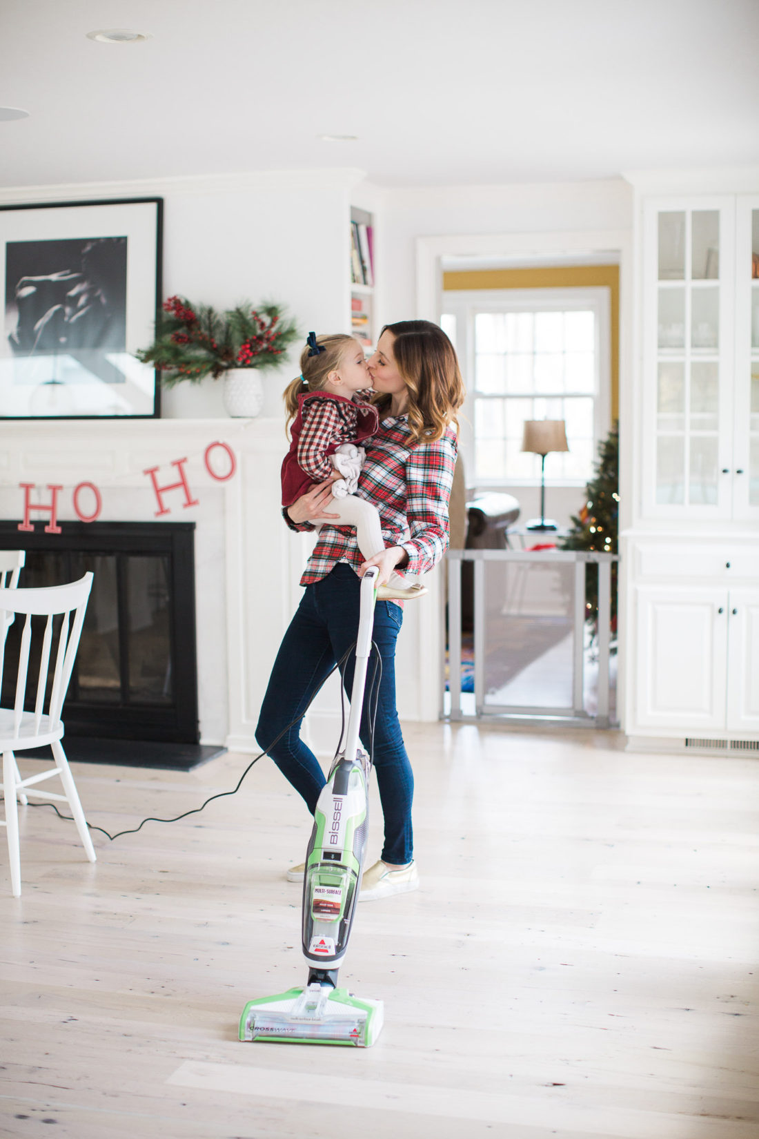 Eva Amurri Martino of lifestyle and motherhood blog Happily Eva After holds her toddler daughter Marlowe in her arms while she vacuums her home and prepares for holiday parties