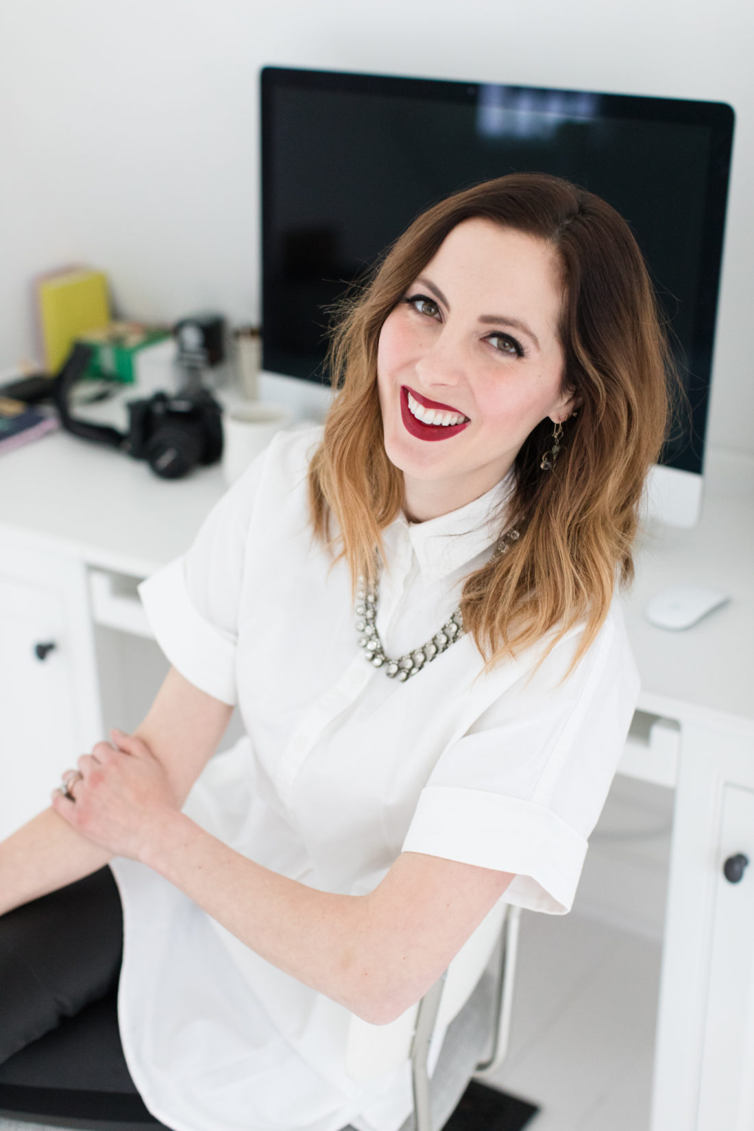 Eva Amurri Martino of lifestlye and motherhood blog Happily Eva After wears a crisp white button down shirt, a statement necklace, and red lipstick at her desk in Connecticut