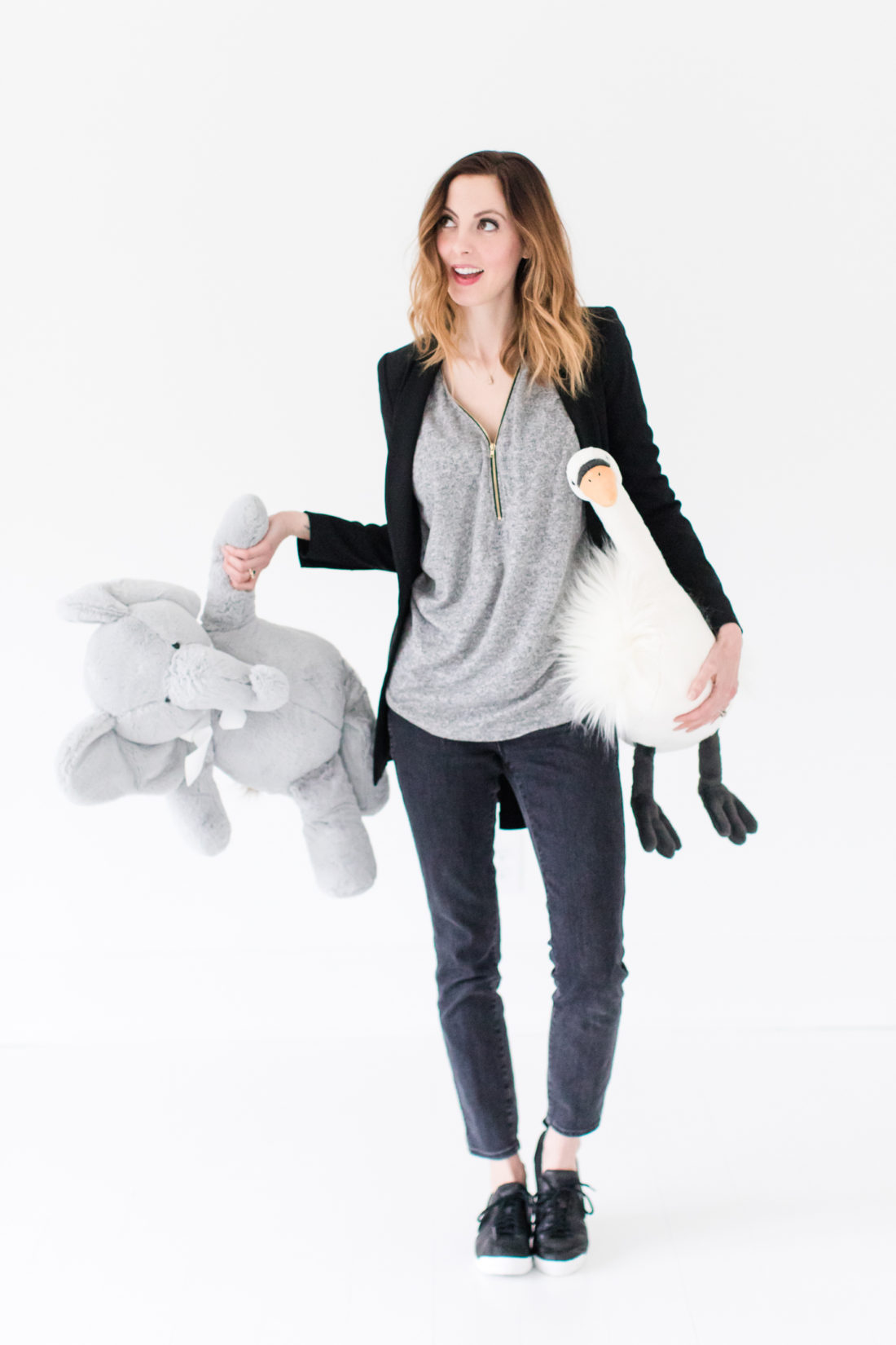 Eva Amurri Martino wears black jeans, a grey top, black nike sneakers, and a black fitted blazer as she cleans up toys in her studio
