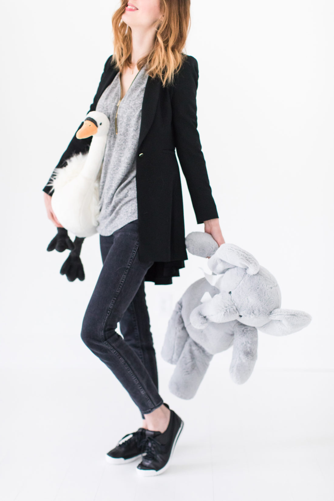 Eva Amurri Martino cleans up stuffed animals wearing a pair of high waisted jeans, a black blazer, and black leather sneakers