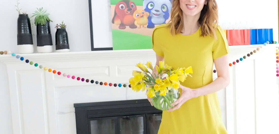 Eva Amurri Martino holds a vase of daffodils, wearing a yellow dress, for a post about entertaining for children