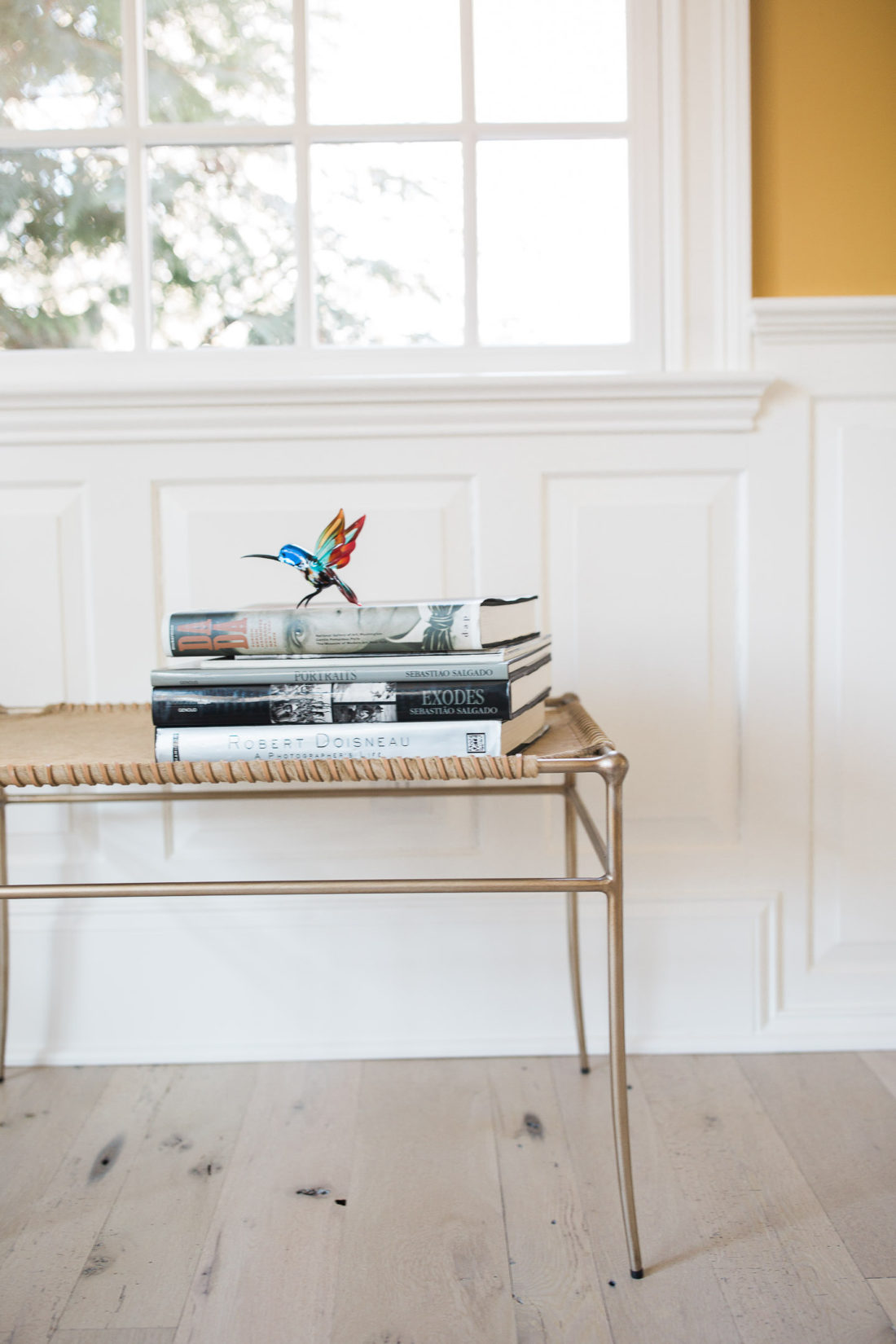 a bench with some books on display sits underneath the window of the living room at Eva Amurri Martino's Connecticut home
