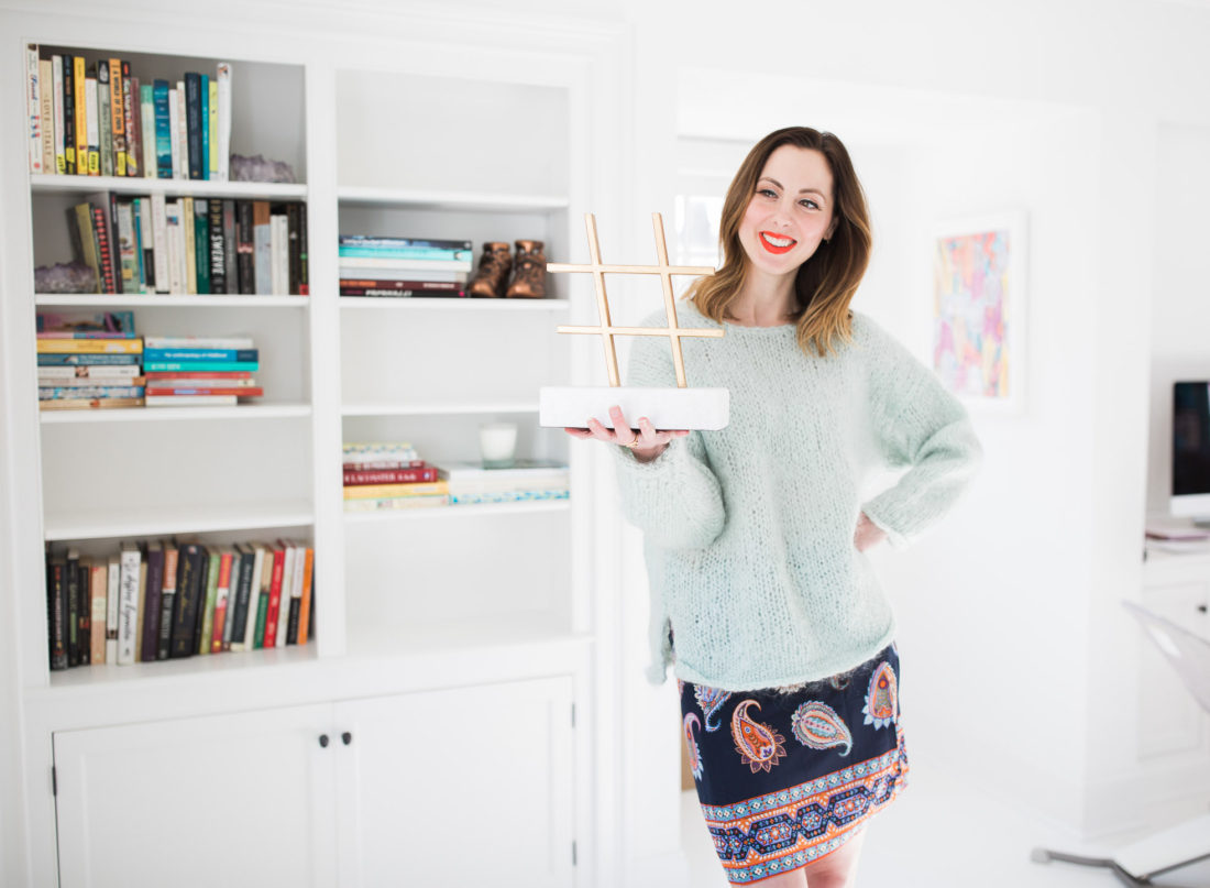 Eva Amurri Martino holds up a marble and brass Hashtag sculpture in the Happily Eva After studio