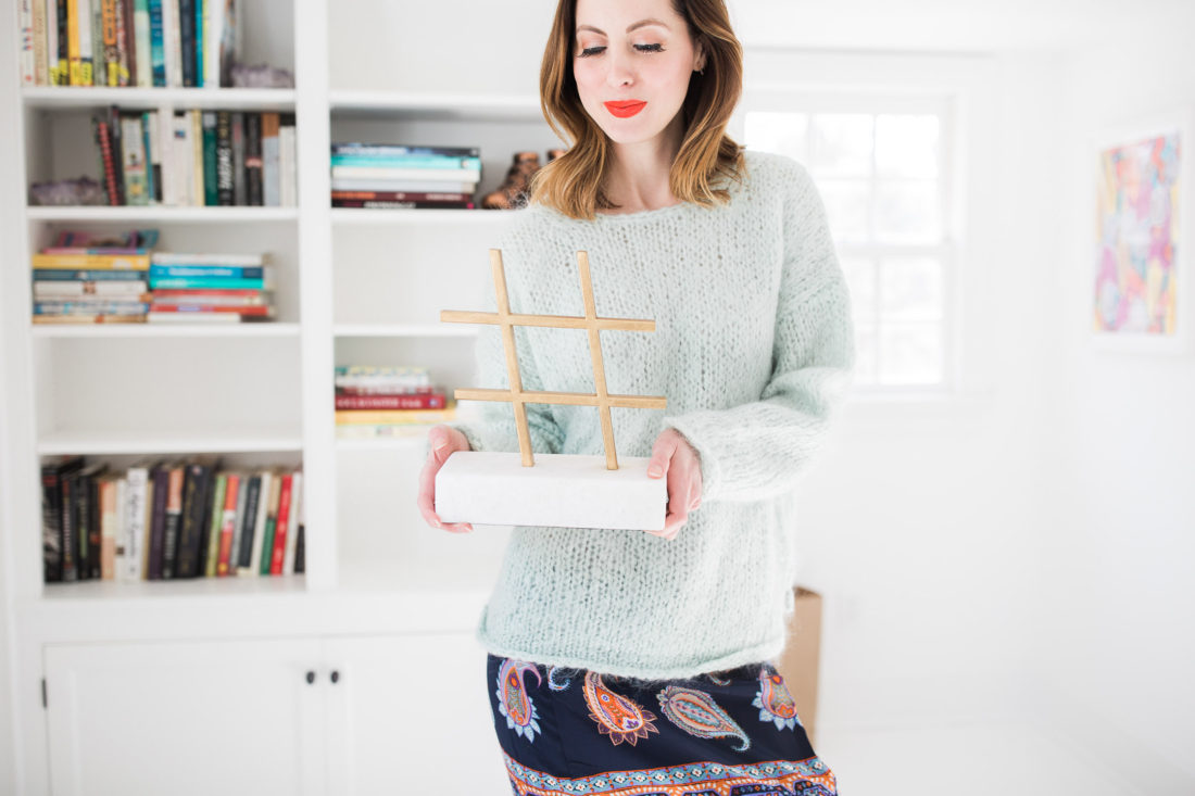 Eva Amurri Martino holds up a gold and marble hashtag sculpture