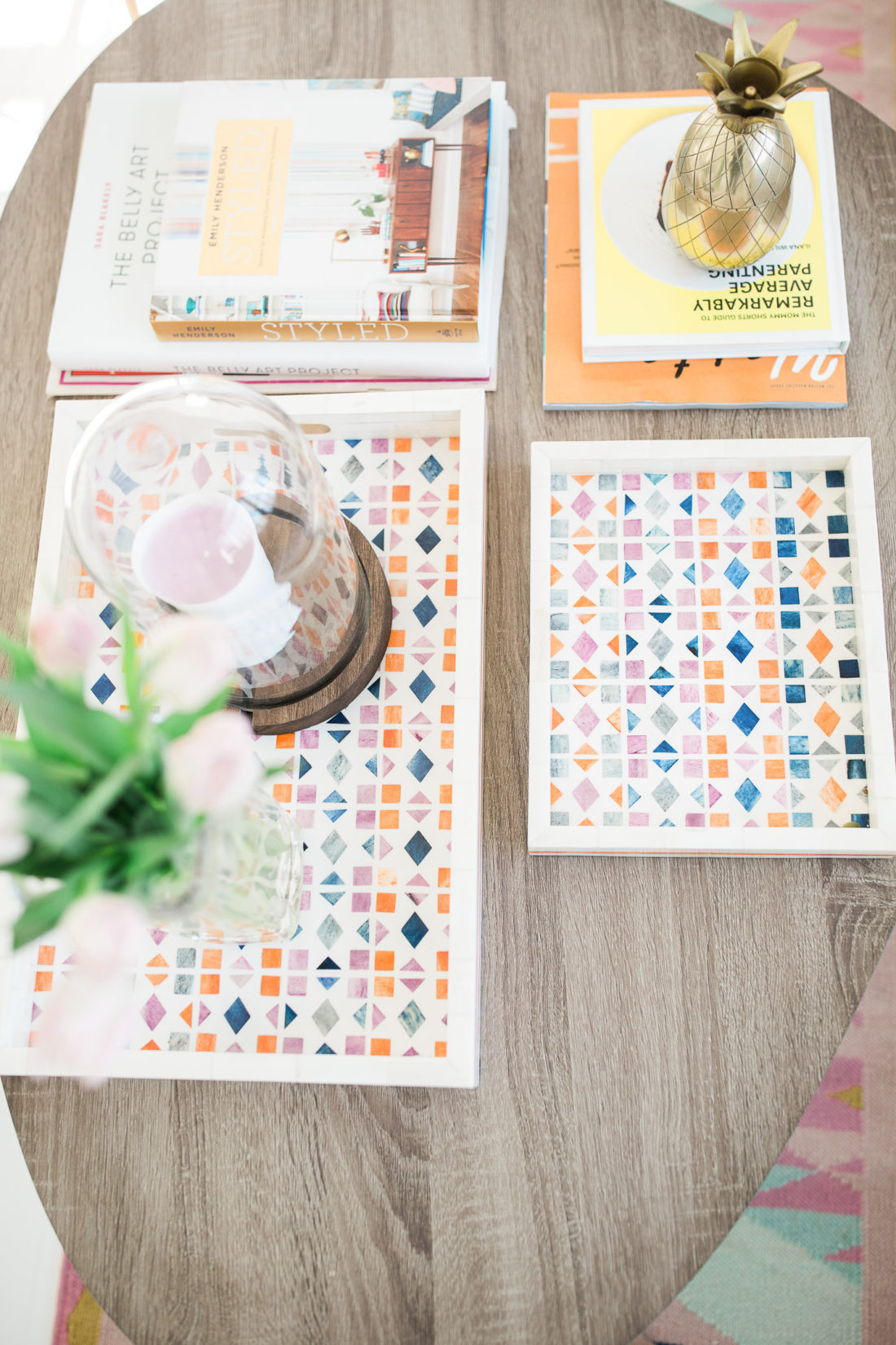 Multicolored decorative trays and stacks of books adorn the coffee table in the Happily Eva After studio