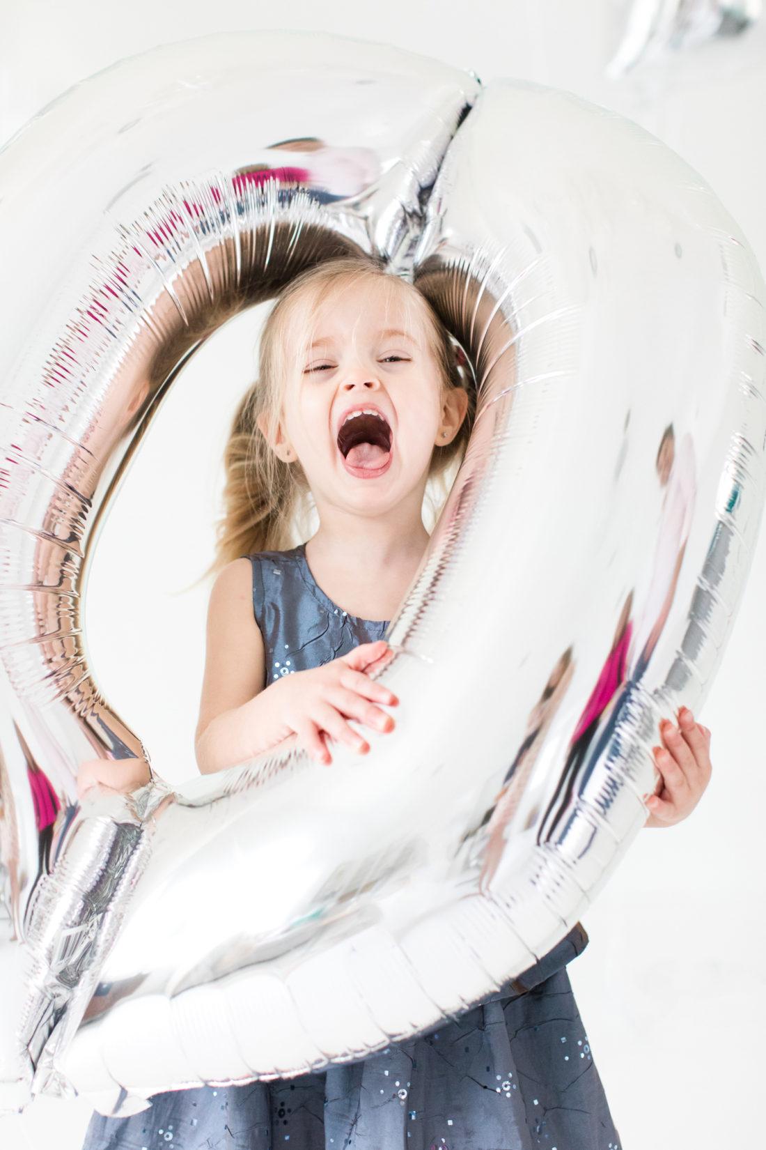 Marlowe Martino sticks her head through a silver balloon