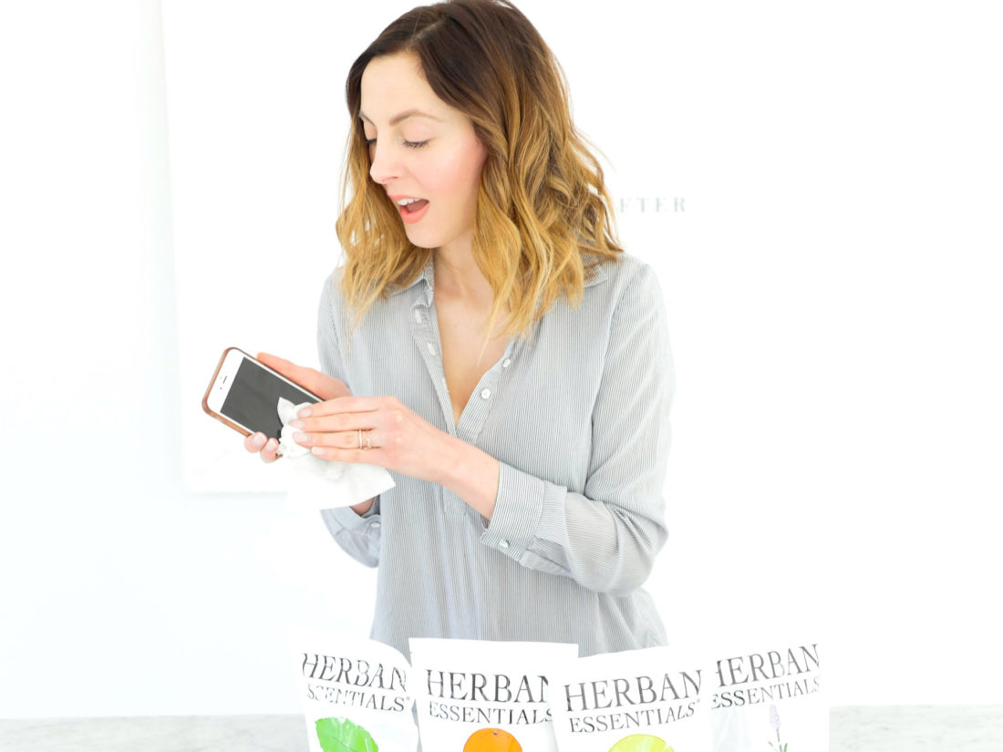 Eva Amurri Martino wipes down her phone with essential oil wipes