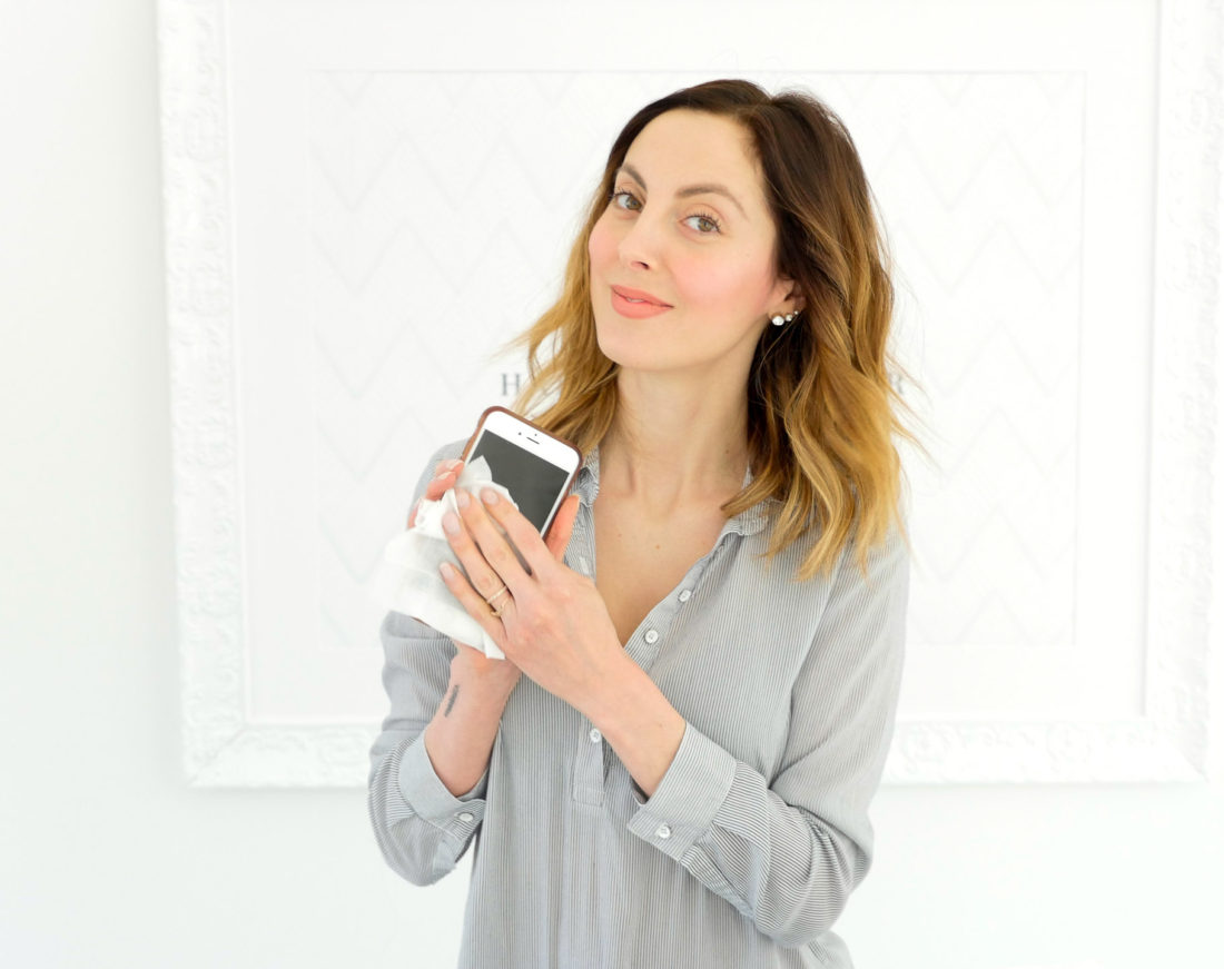 Eva Amurir Martino wipes down her phone with Essential oil wipes