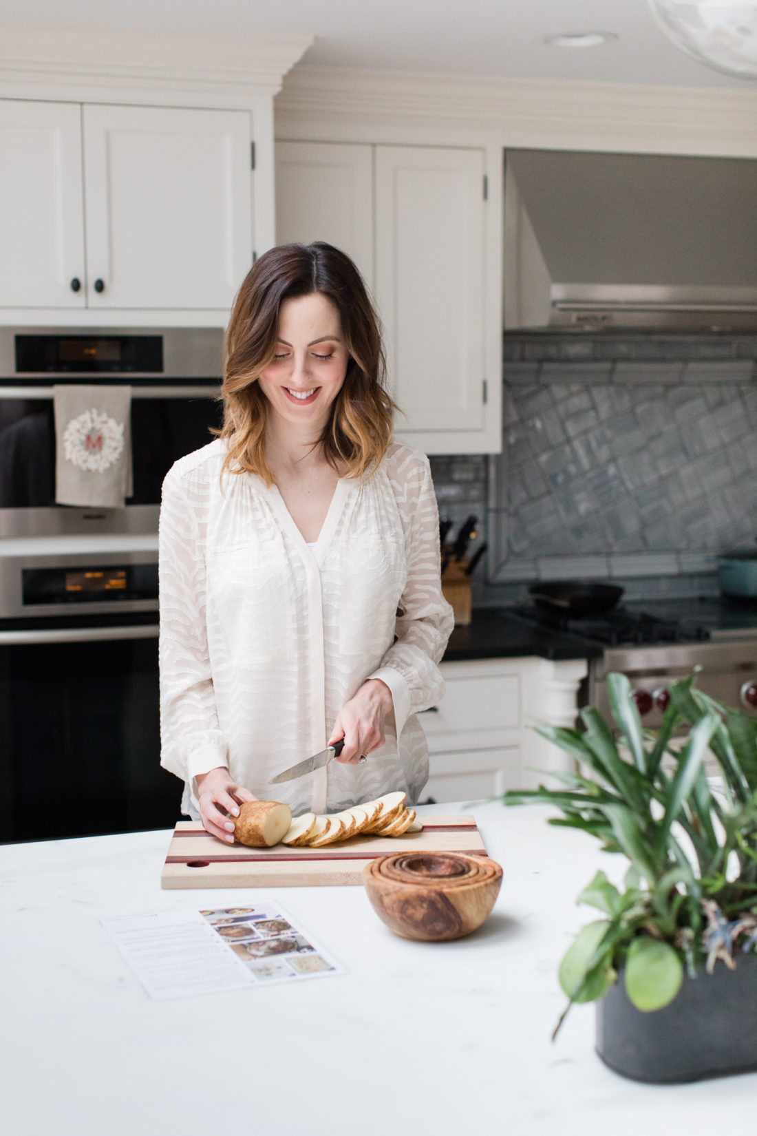 Eva Amurri Martino slices rounds of potatoes in her kitchen