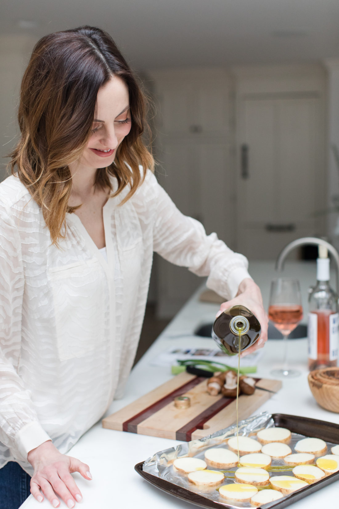 Eva Amurri Martino drizzles olive oil over sliced potatoes