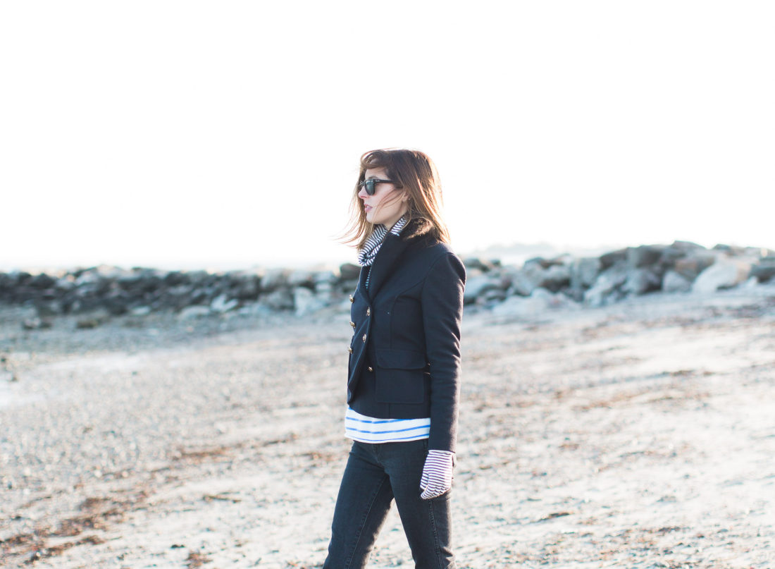 Eva Amurri Martino walks on Compo Beach in Connecticut in the winter time, wearing a navy blue peacoat and black wayfarers