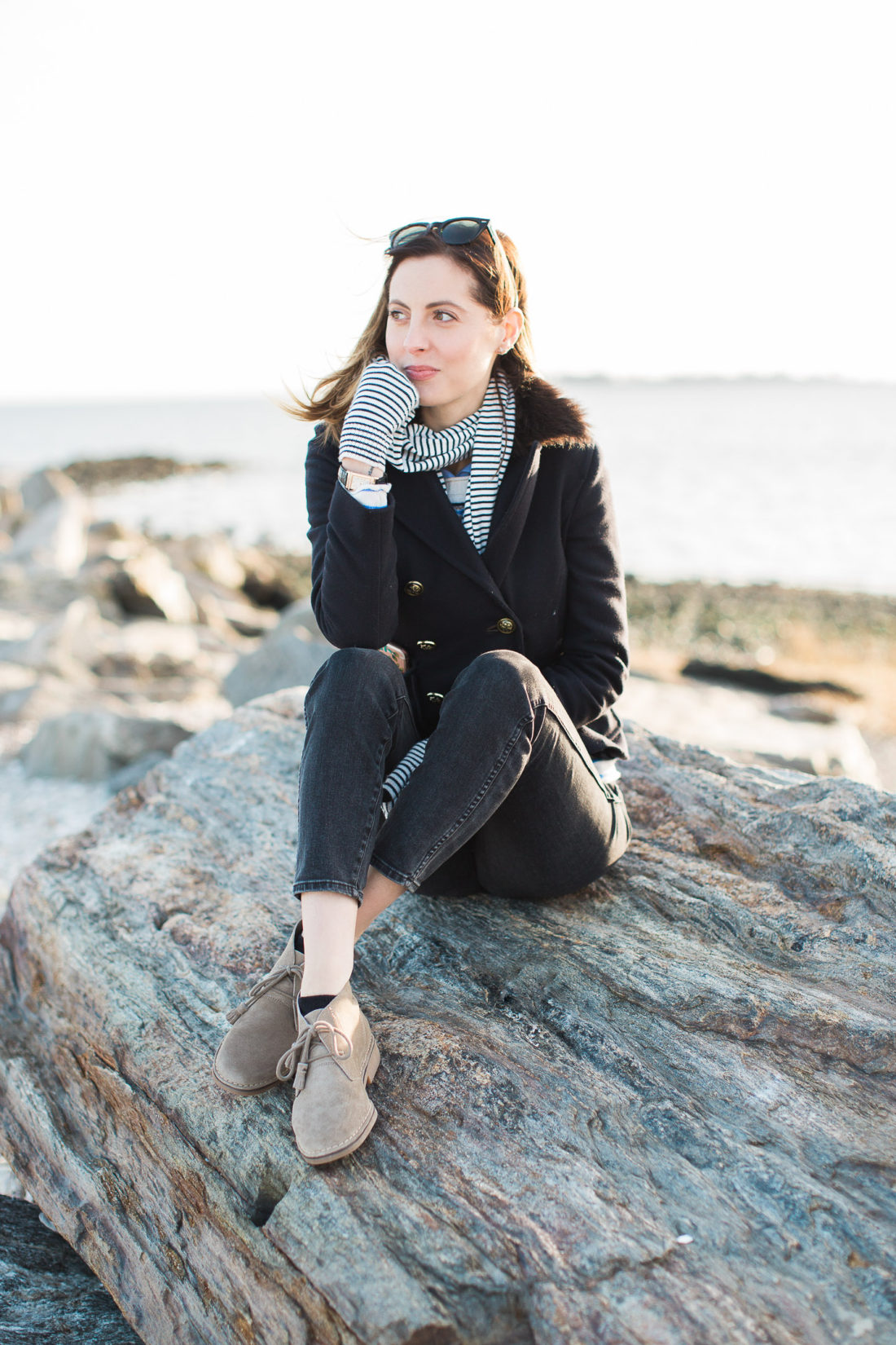 Eva Amurri Martino sits on a boulder on the beach in Connecticut with the long island sound behind her