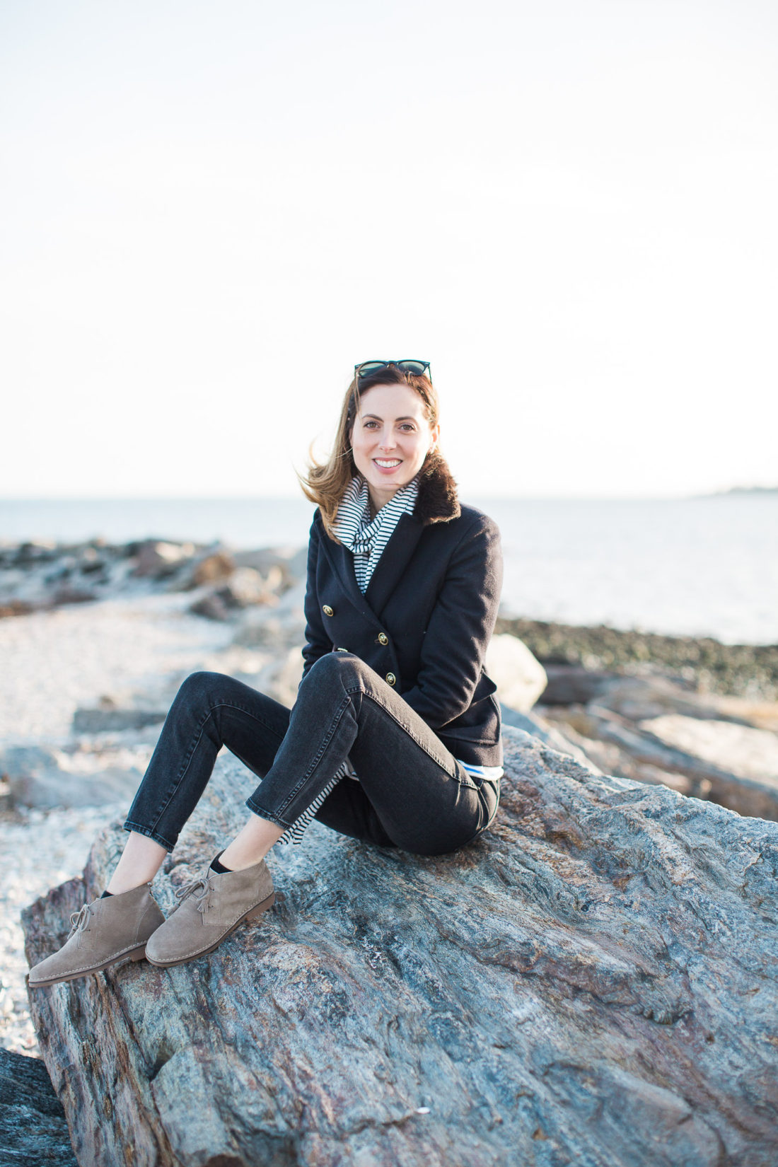 Eva Amurri Martino sits on a boulder on Compo Beach in Connecticut with the Long Island Sound behind her