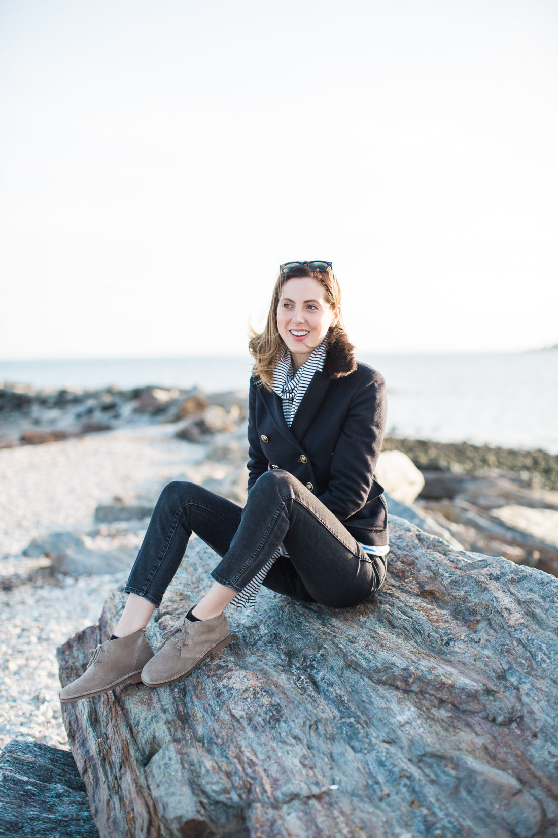 Eva Amurri Martino sits on the rocks at Compo Beach wearing a navy blue peacoat and striped scarf