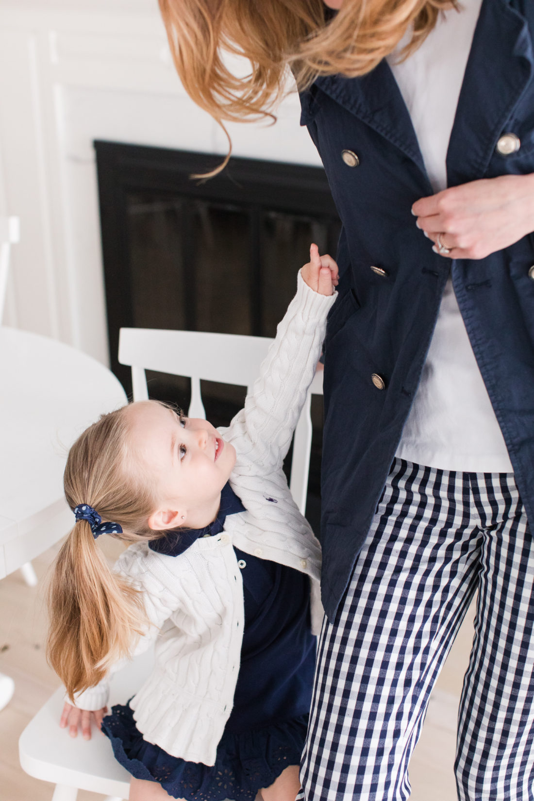 Marlowe Martino points to the buttons on her Mom's navy blue trenchcoat