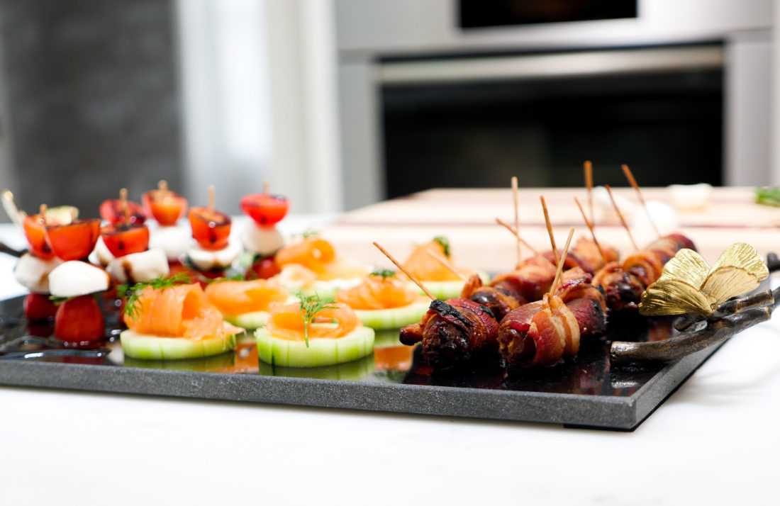 Caprese Salad Bites, Smoked Salmon cucumber disks, and bacon wrapped dates sit on an appetizer tray in Eva Amurri Martino's kitchen