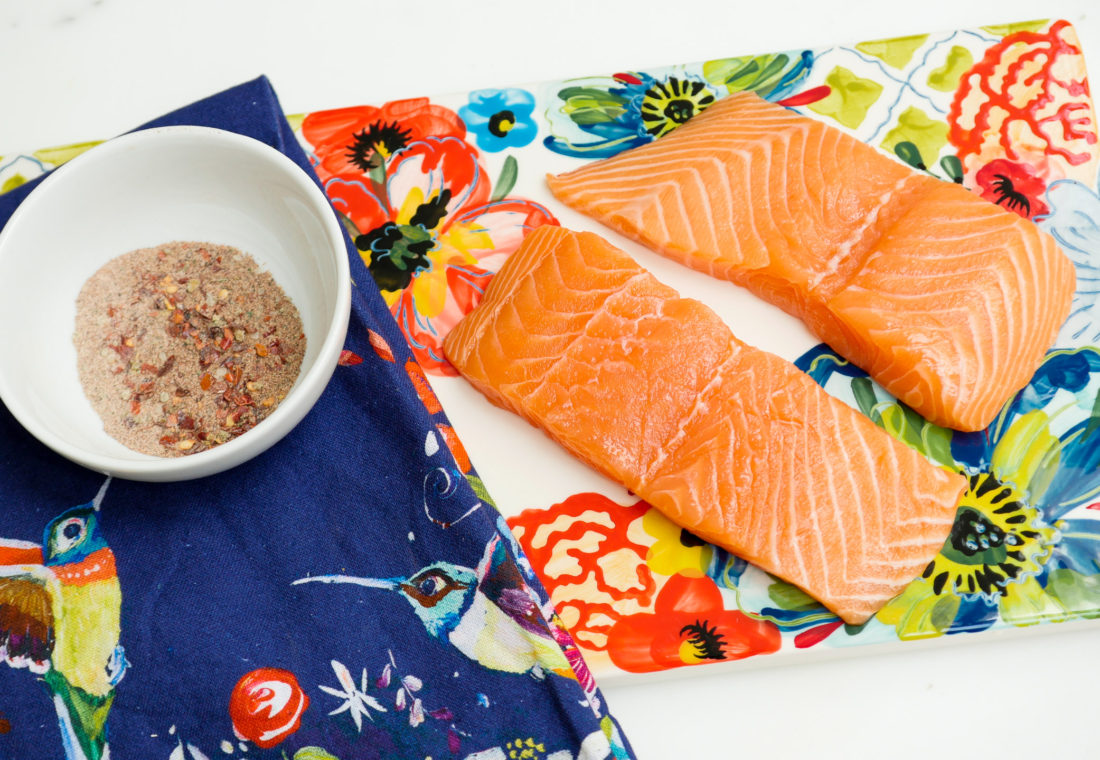 Raw salmon sits next to a bowl of Mexican Spice rub for Eva Amurri Martino's healthy salmon bowls
