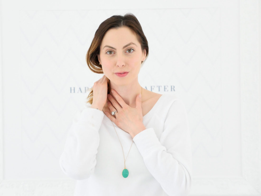 Eva Amurri Martino wears a white sweatshirt and applies anti aging neck serum