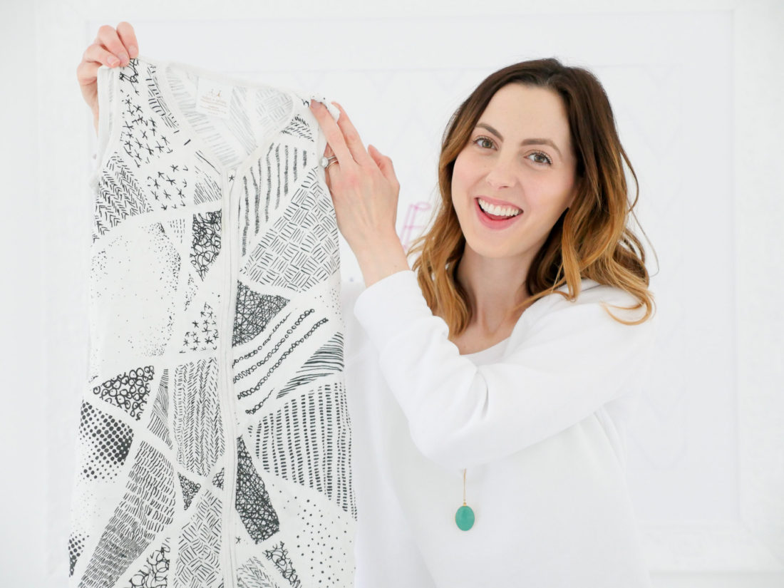 Eva Amurri Martino holds up a black and white patterned Aden & Anais sleep sack