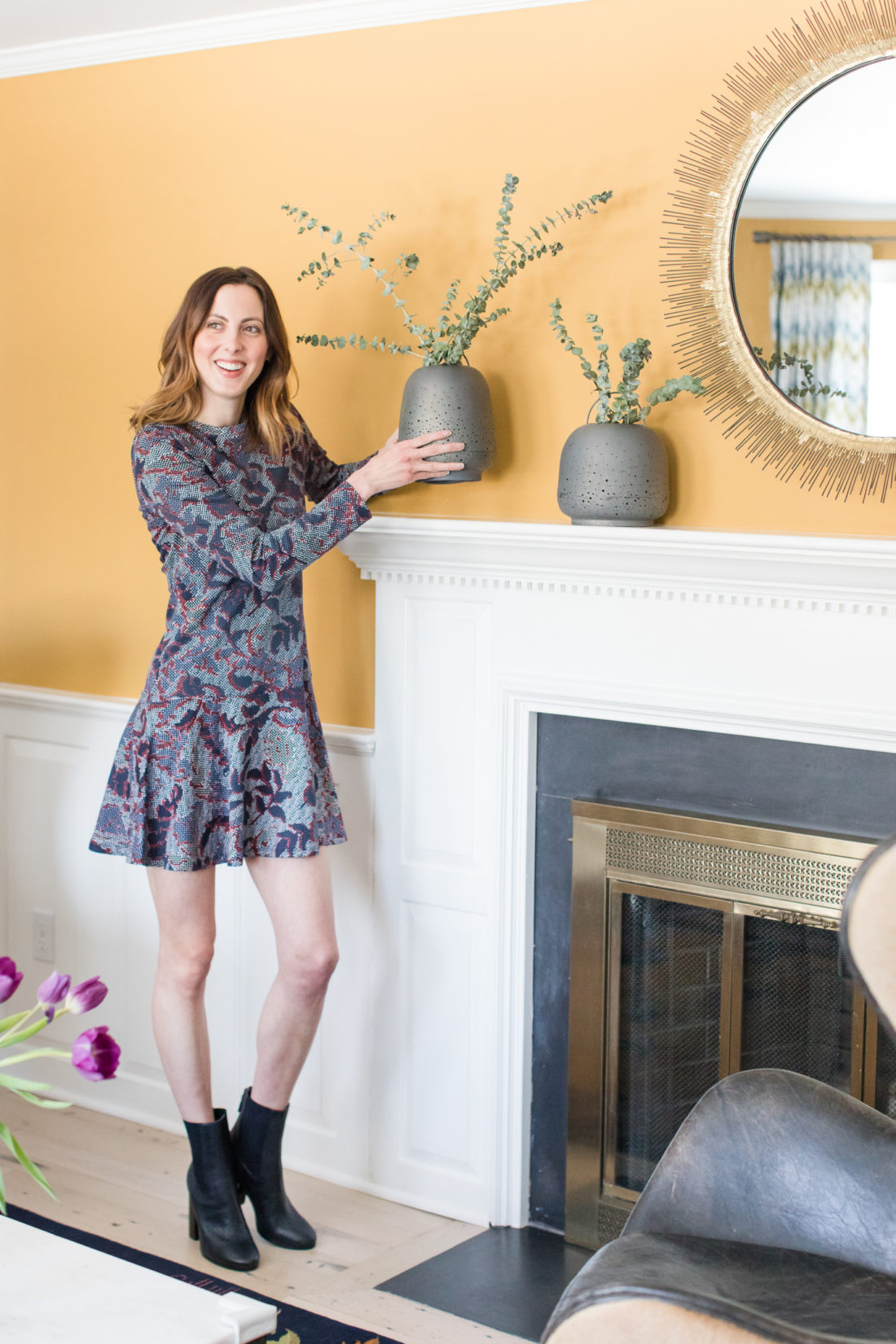 Eva Amurri Martino of lifestyle and motherhood blog Happily Eva After sets some decor on the mantle in the formal living room of her Connecticut home