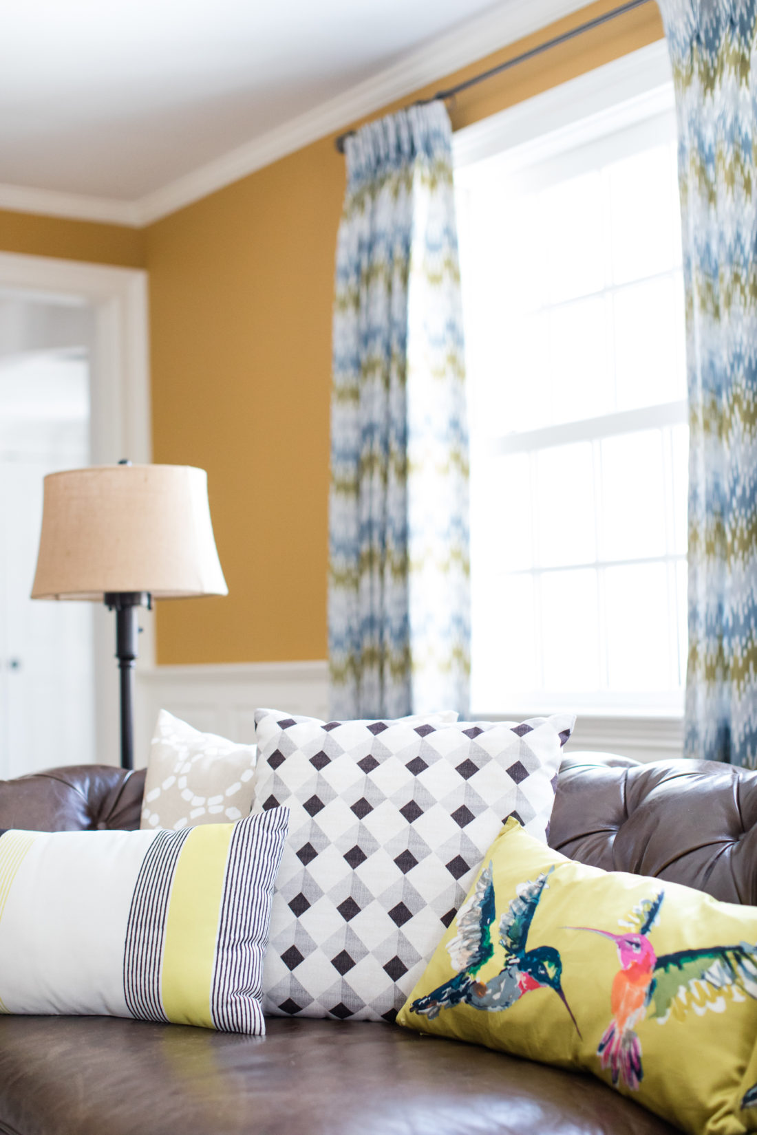 Black, white, natural, and yellow patterned couch pillows are scattered on the brown leather sofa in the formal living room of Eva Amurri Martino's connecticut home
