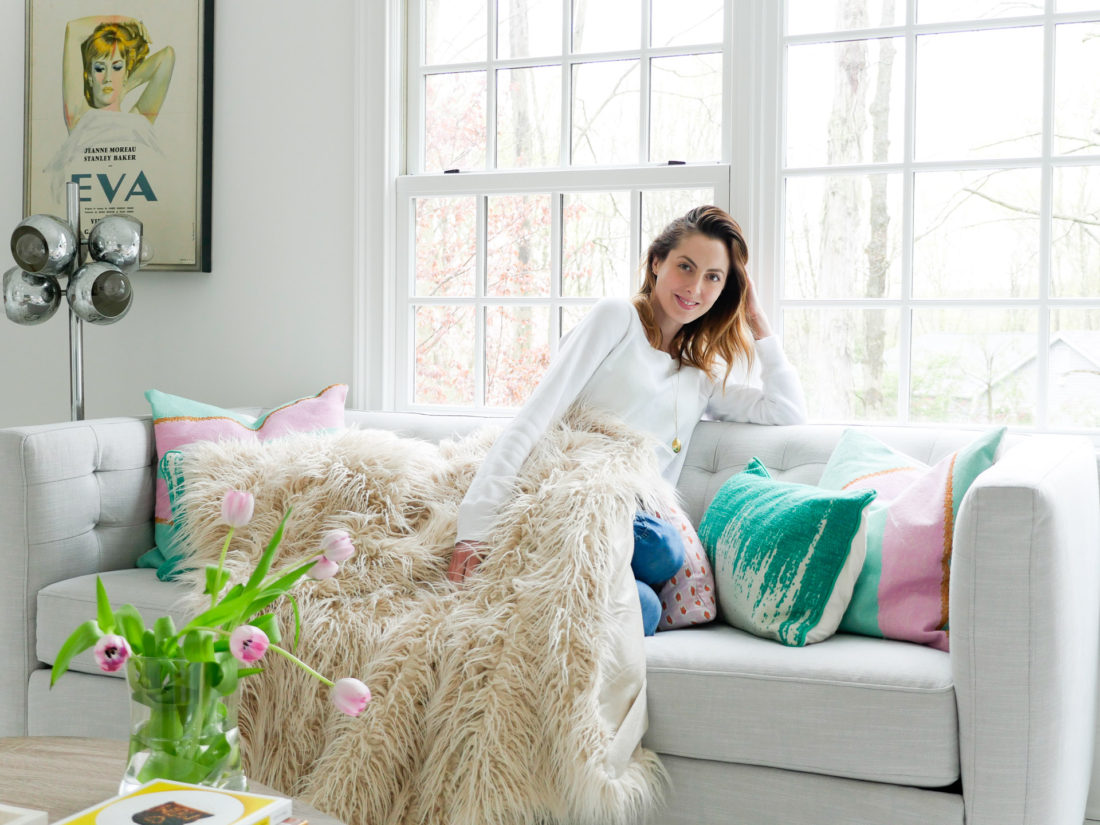 Eva Amurri Martino relaxes on the couch in the Happily Eva After studio wearing a white sweatshirt
