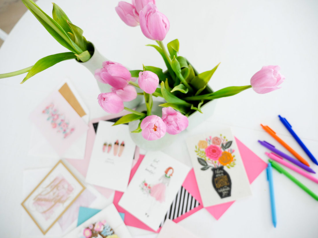 Colorful mother's day cards surround a bouquet of pink tulips
