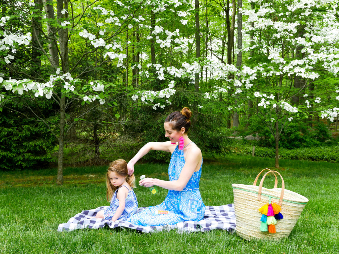 Eva Amurri Martino sits on a picnic blanket with daughter Marlowe and applies bug spray
