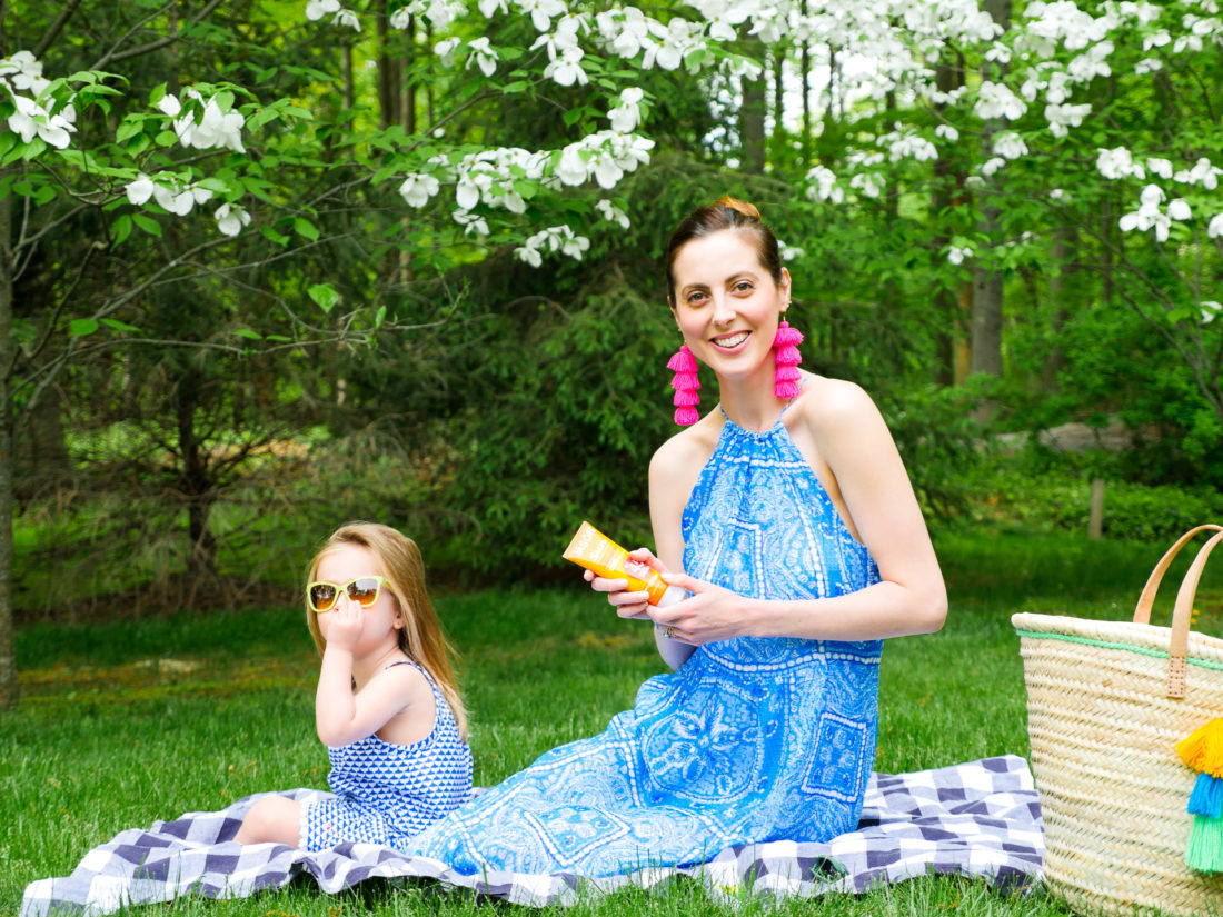 Eva Amurri Martino and daughter Marlowe sit on a picnic blanket on the grass and apply sunscreen
