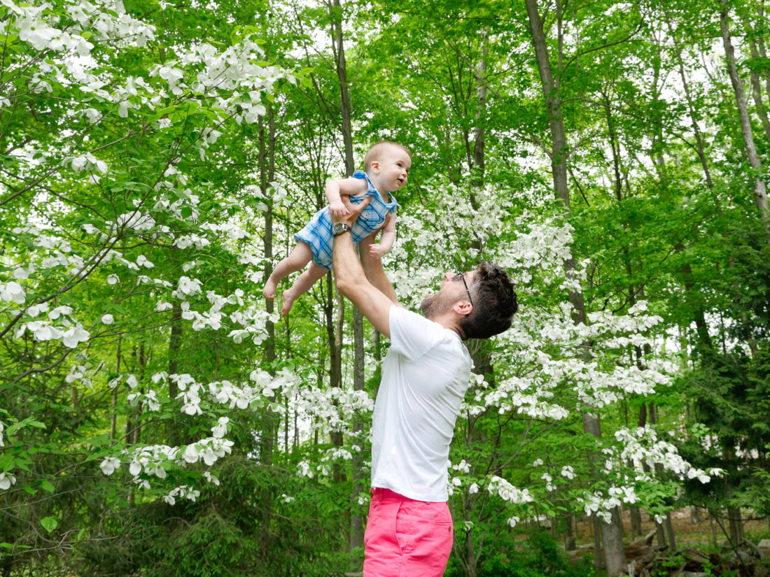Kyle Martino lifts son Major in to the air, surrounded by greenery