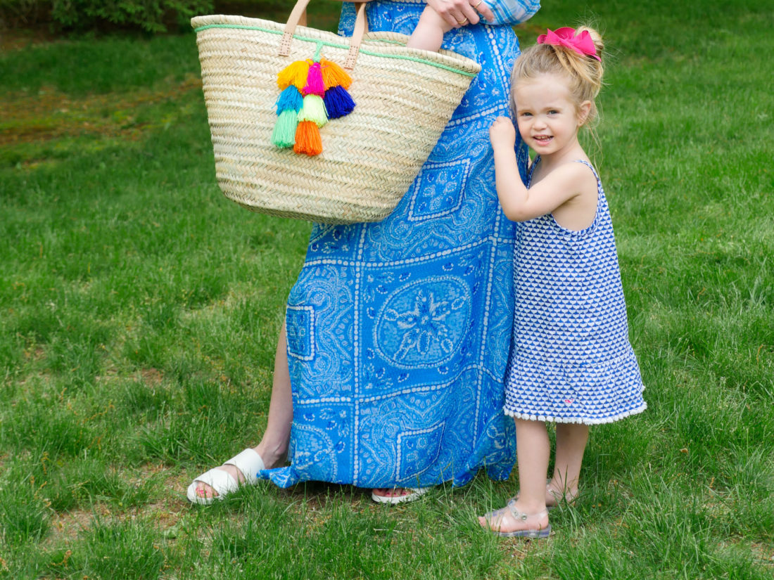 Marlowe Martino wears a blue and white patterned dress and clings to her mother's leg