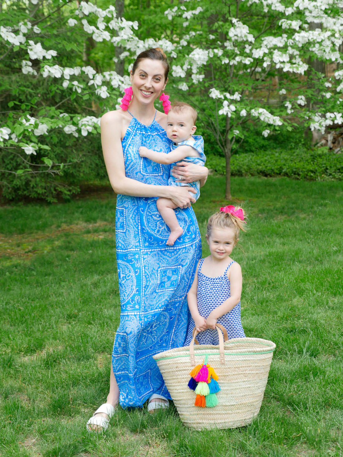 Eva Amurri Martino stands with her children in the countryside wearing a blue maxi dress and magenta tassel earrings