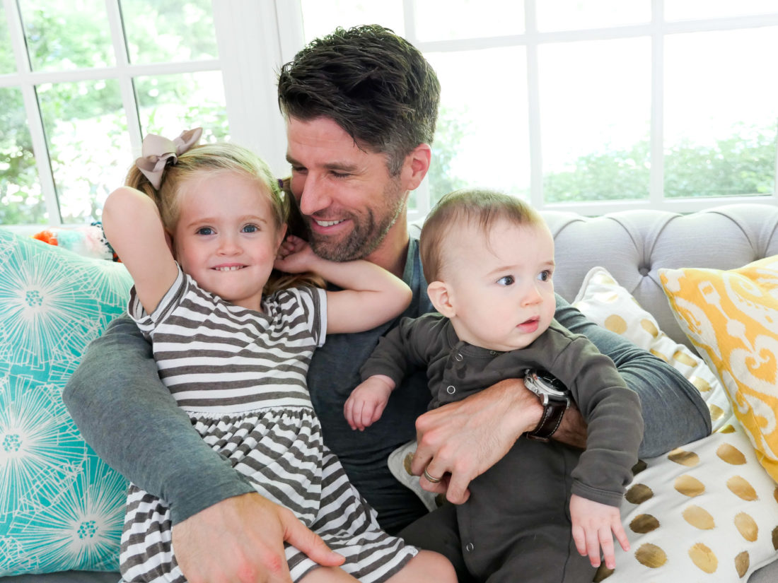 Kyle Martino sits on the couch with his two children, Marlowe and Major, nestled on his lap