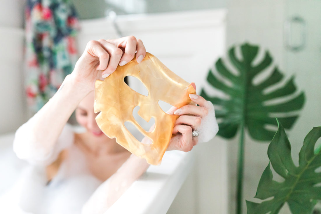 Eva Amurri Martino holds up a 24 karat gold sheet mask