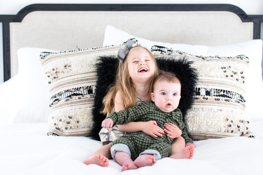 Marlowe Martino holds her little brother Major in her lap on her parents' bed