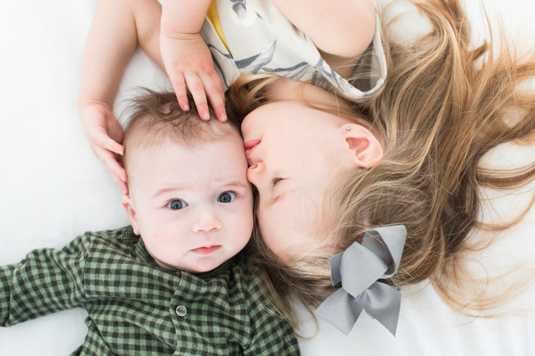 Marlowe Martino holds her baby brother and gives him a sweet kiss on the head