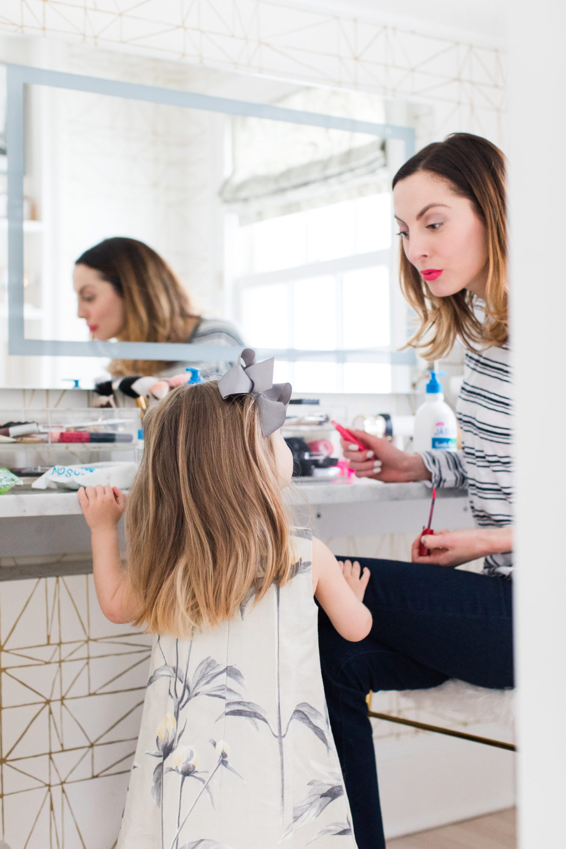 Eva Amurri martino applies makeup in her Glam Room while two year old daughter Marlowe looks on