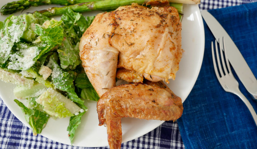 Juicy and delicious beer can chicken rests on a plate with ceasar salad and asparagus