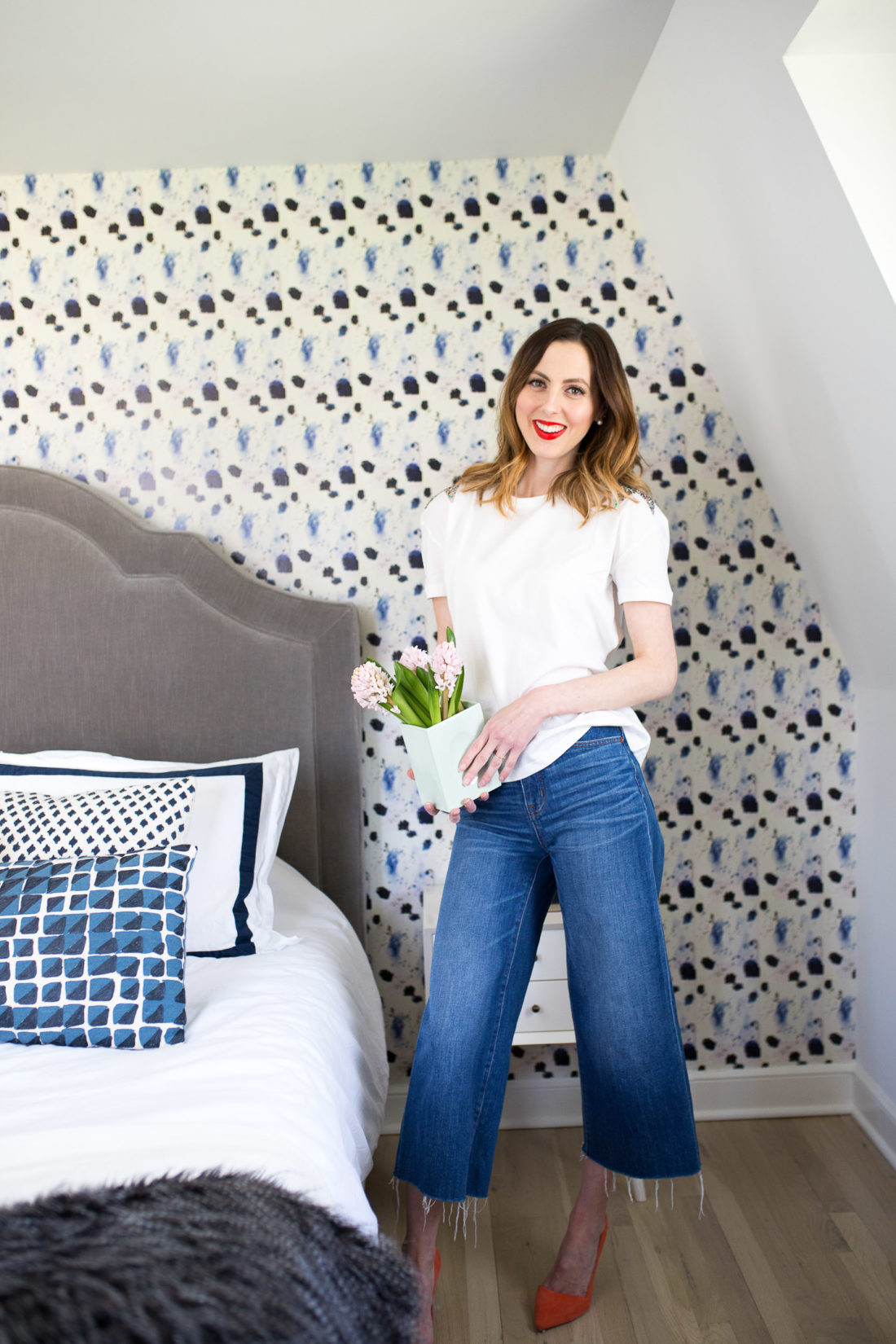 Eva Amurri Martino holds a vase of flowers in her newly updated guest bedroom at home in connectiut