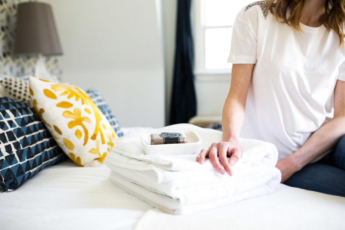 Eva Amurri Martino rests her arm on a stack of bright white guest towels