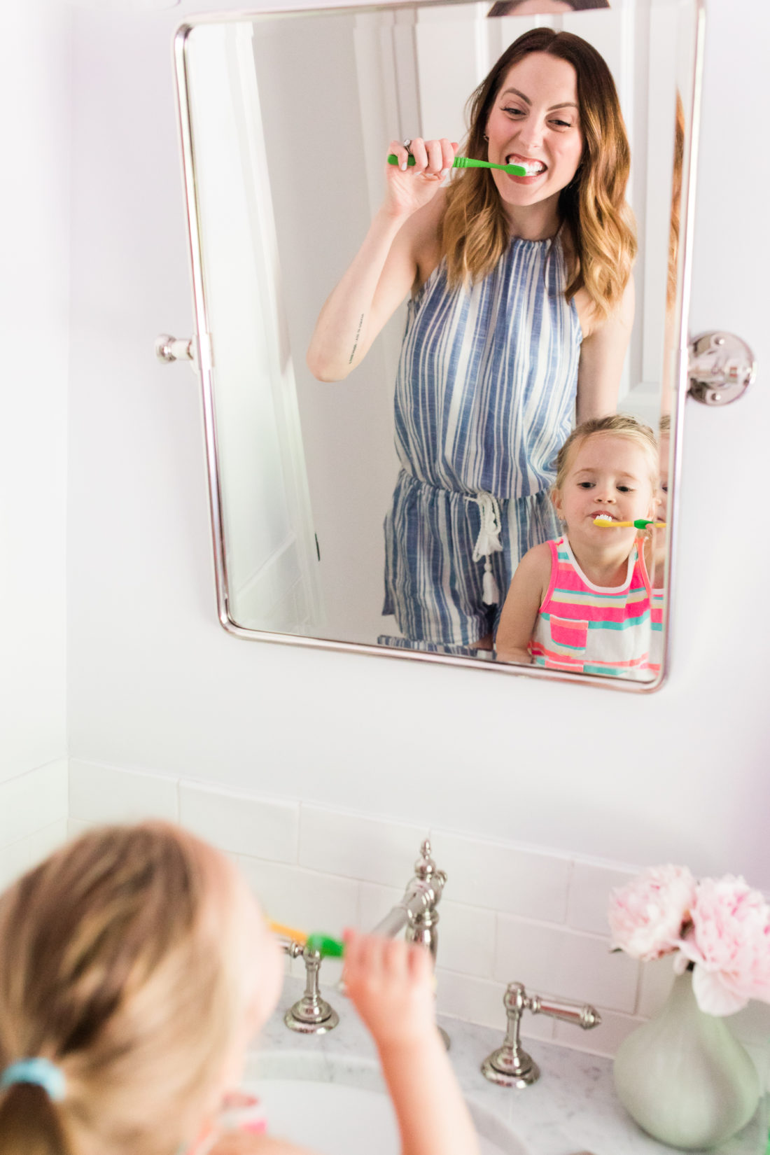 Eva Amurri Martino wears a blue and white striped romper and brushes her teeth with two year old daughter, Marlowe, in the bathroom of their Connecticut home