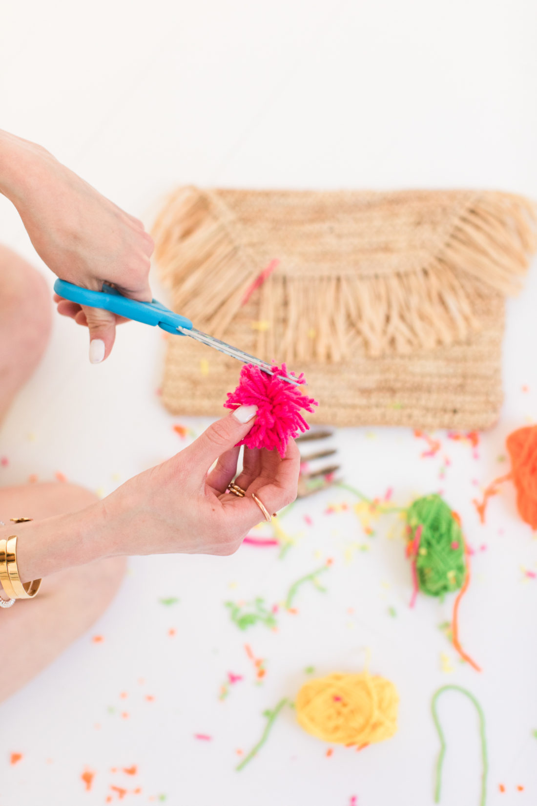 Eva Amurri Martino of lifestyle and motherhood blog Happily Eva After shares a DIY pom pom clutch for Summer