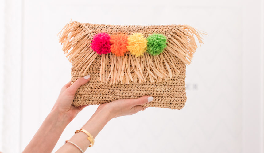 Eva Amurri Martino holds up a multicolored DIY pom pom straw clutch