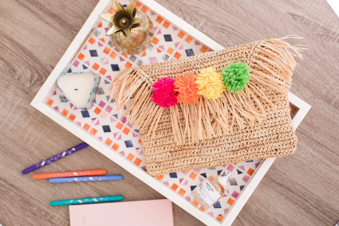 A multicolored pom pom clutch sits on a table with a bone inlay tray, a journal, and several multicolored pens